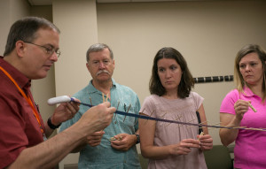 Rico Tyler (from left) gets assistance creating his wave machine from NSCF Scholars Bruce Boehne, Jill Henry and Amy Long on Wednesday, June 8. The wave machine can be used as a physical representation of amplitude and also as a double helix DNA  model. (Photo by Tucker Allen Covey)