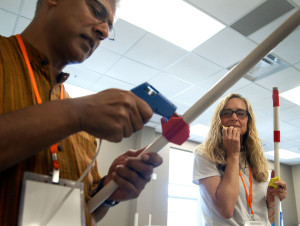 Santosh Zachariah from the Evergreen School in Shoreline, Washington, attaches foam fins to his rocket while Melissa Harris of Warren East Middle School in Bowling Green waits to use the hot glue gun, Tuesday, June 7. The simple rockets took about thirty minutes to construct. (Photo by Sam Oldenburg)